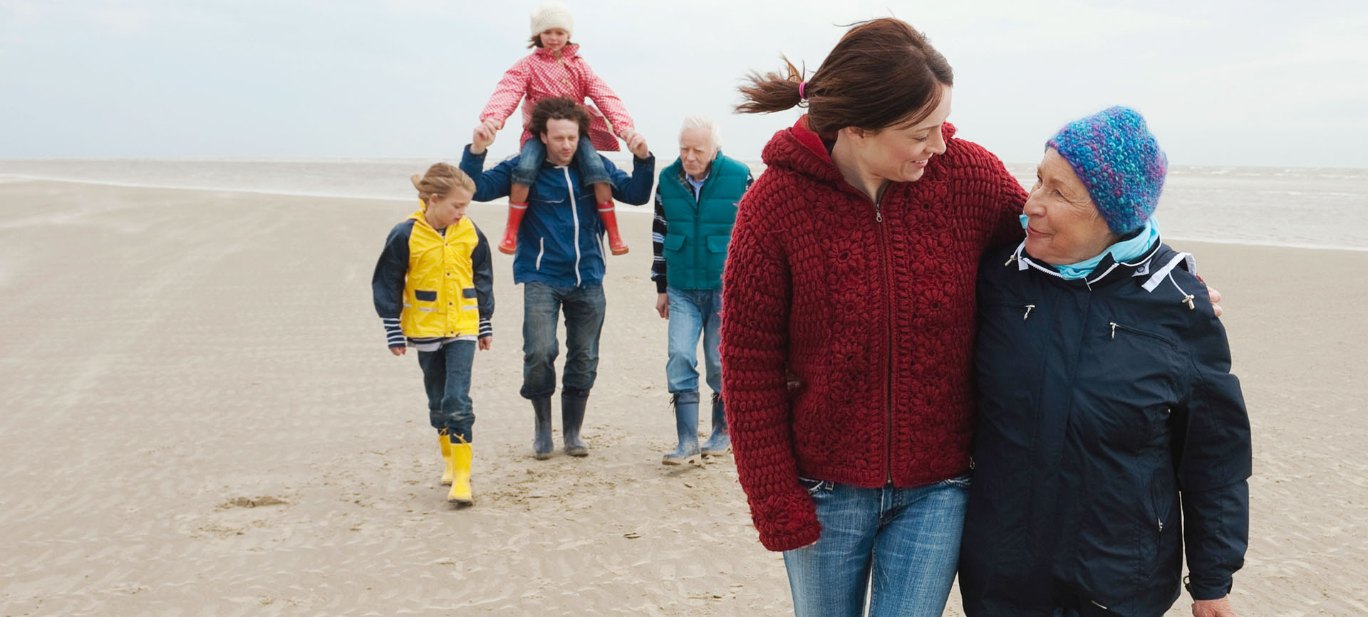 A younger and older woman walking together with two men and two children behind them.